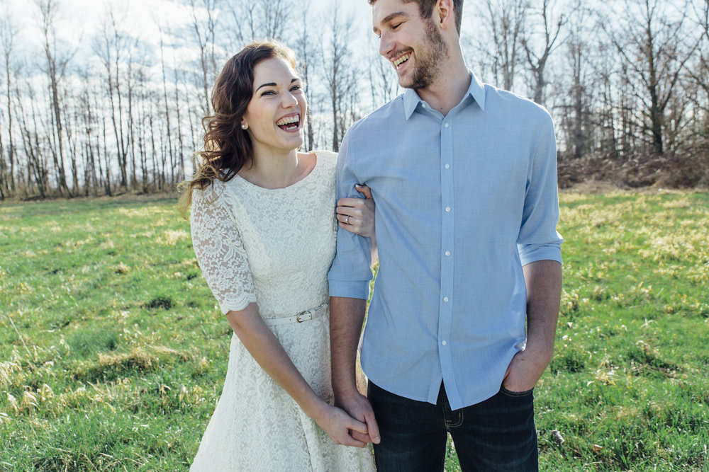 A sunny spring engagement session at Hovander Homestead in Ferndale, Washington. www.mimsicalphotography.com by Christina Voorhorst #bunny #engagement #spring #engagement #truck #country #lace #puddles #mimsicalphotography #holdinghands #field #laughter #joy #emotion #blue