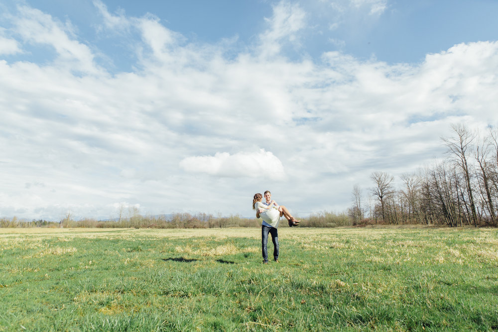 A sunny spring engagement session at Hovander Homestead in Ferndale, Washington. www.mimsicalphotography.com by Christina Voorhorst Man carrying girl through field mountains in the background, lots of clouds #bunny #engagement #spring #engagement #truck #country #lace #puddles #mimsicalphotography