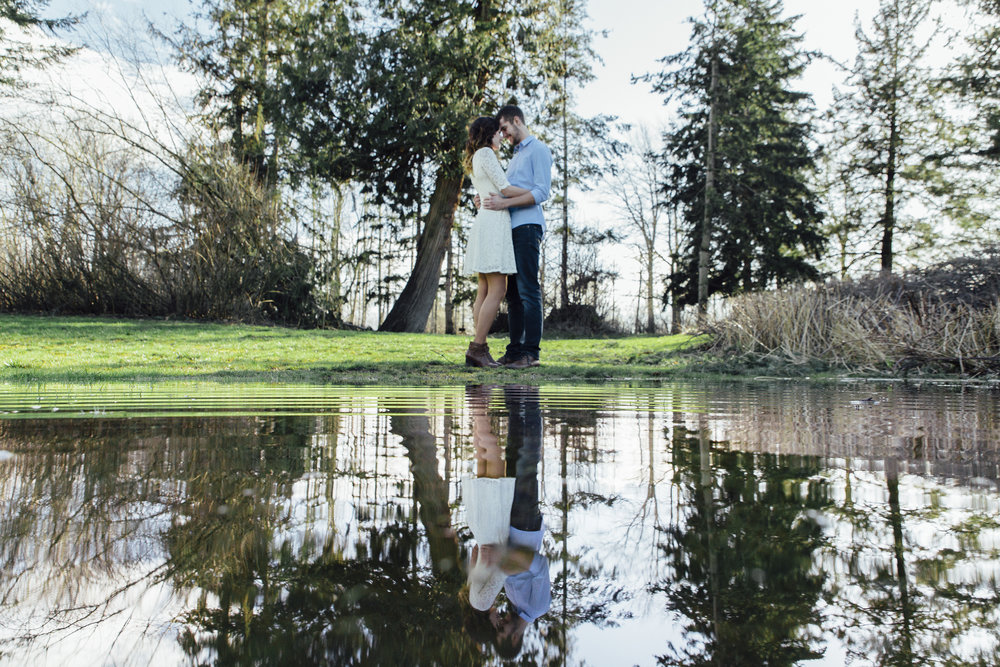 A sunny spring engagement session at Hovander Homestead in Ferndale, Washington. www.mimsicalphotography.com by Christina Voorhorst Couple looking at each other from across a puddle  #bunny #engagement #spring #engagement #truck #country #lace #puddles #mimsicalphotography #romantic #emotion #connection #pose #coupleposes #reflection