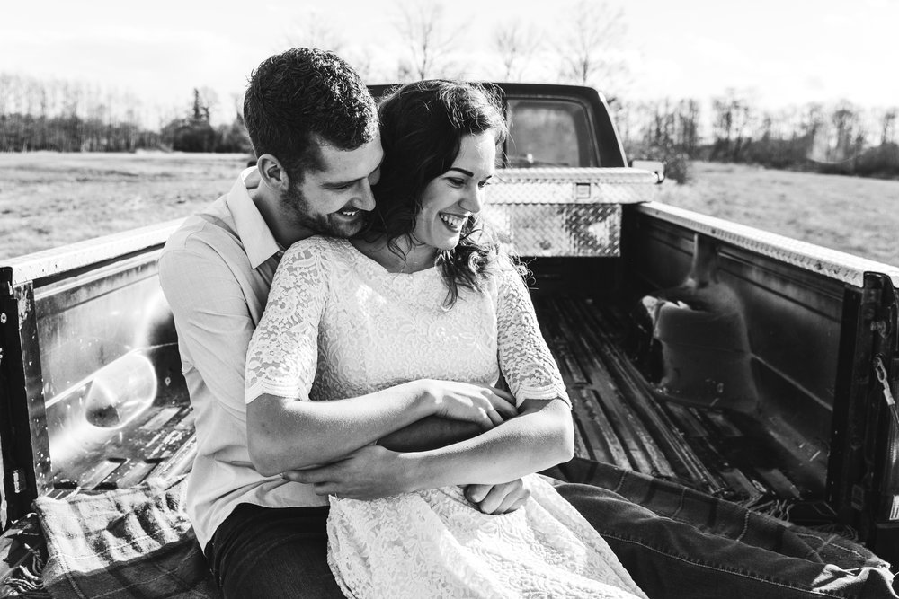 A sunny spring engagement session at Hovander Homestead in Ferndale, Washington. www.mimsicalphotography.com by Christina Voorhorst  Couple sitting in Ford Truck bed, laughing  #bunny #engagement #spring #engagement #truck #country #lace #puddles #mimsicalphotography #romantic #emotion #connection #pose #coupleposes