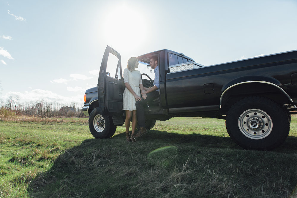 A sunny spring engagement session at Hovander Homestead in Ferndale, Washington. www.mimsicalphotography.com by Christina Voorhorst. Couple standing by black Ford truck#bunny #engagement #spring #engagement #truck #country #lace #puddles #mimsicalphotography #romantic #emotion #connection #pose #coupleposes
