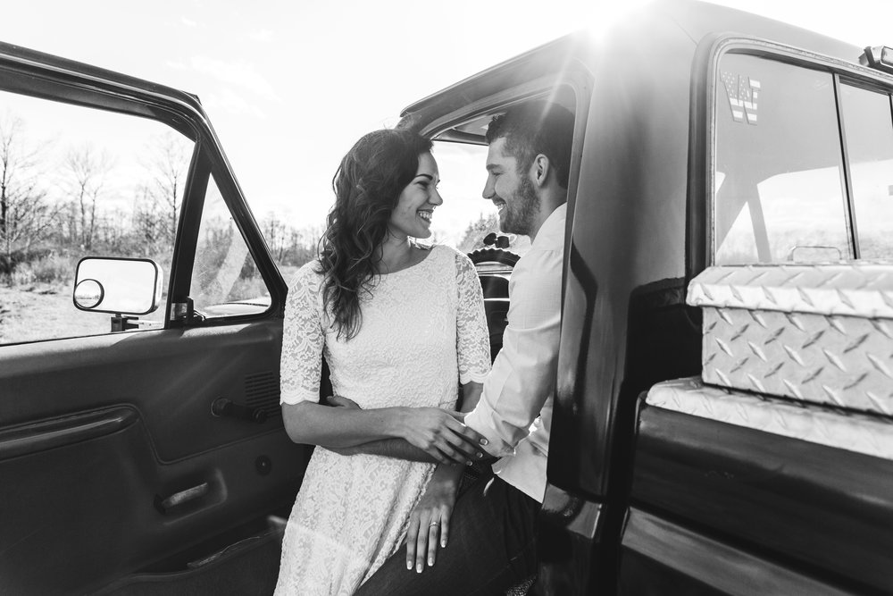 A sunny spring engagement session at Hovander Homestead in Ferndale, Washington. www.mimsicalphotography.com by Christina Voorhorst Couple sitting in Ford truck with the door open #bunny #engagement #spring #engagement #truck #country #lace #puddles #mimsicalphotography #romantic #emotion #connection #pose #coupleposes