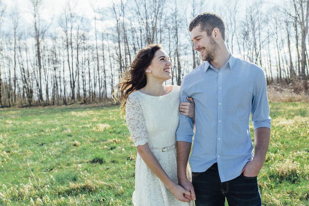 A sunny spring engagement session at Hovander Homestead in Ferndale, Washington. Couple holding hands in a field www.mimsicalphotography.com by Christina Voorhorst #bunny #engagement #spring #engagement #truck #country #lace #puddles #mimsicalphotography #holdinghands