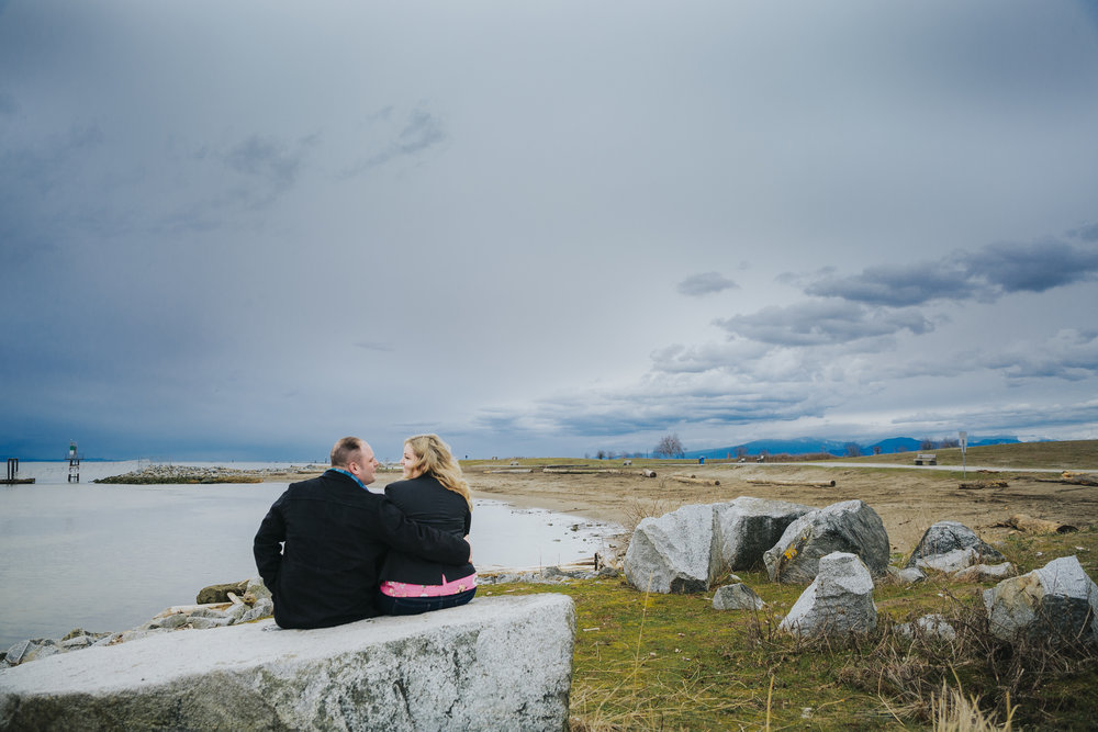 Cloudy engagement session at Garry Point Park in Richmond, BC. Couple sitting on rock  Photography by Christina Voorhorst of Mimsical Photography  #westcoastphotographer #engagement #ring #couple #ocean #cloud #overcast #romantic #poses #stormy
