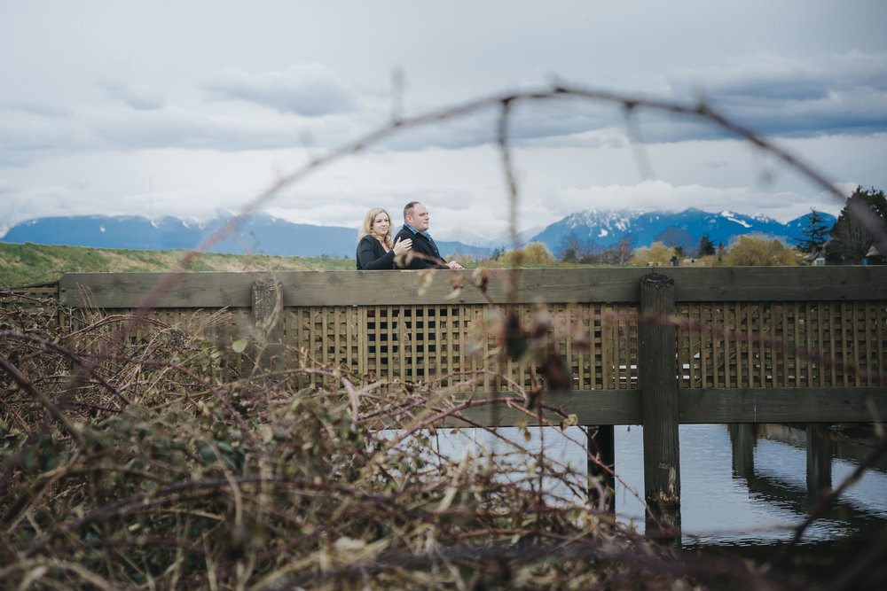 Cloudy engagement session at Garry Point Park in Richmond, BC.  Photography by Christina Voorhorst of Mimsical Photography  #westcoastphotographer #engagement #ring #couple #ocean #cloud #overcast #romantic #poses
