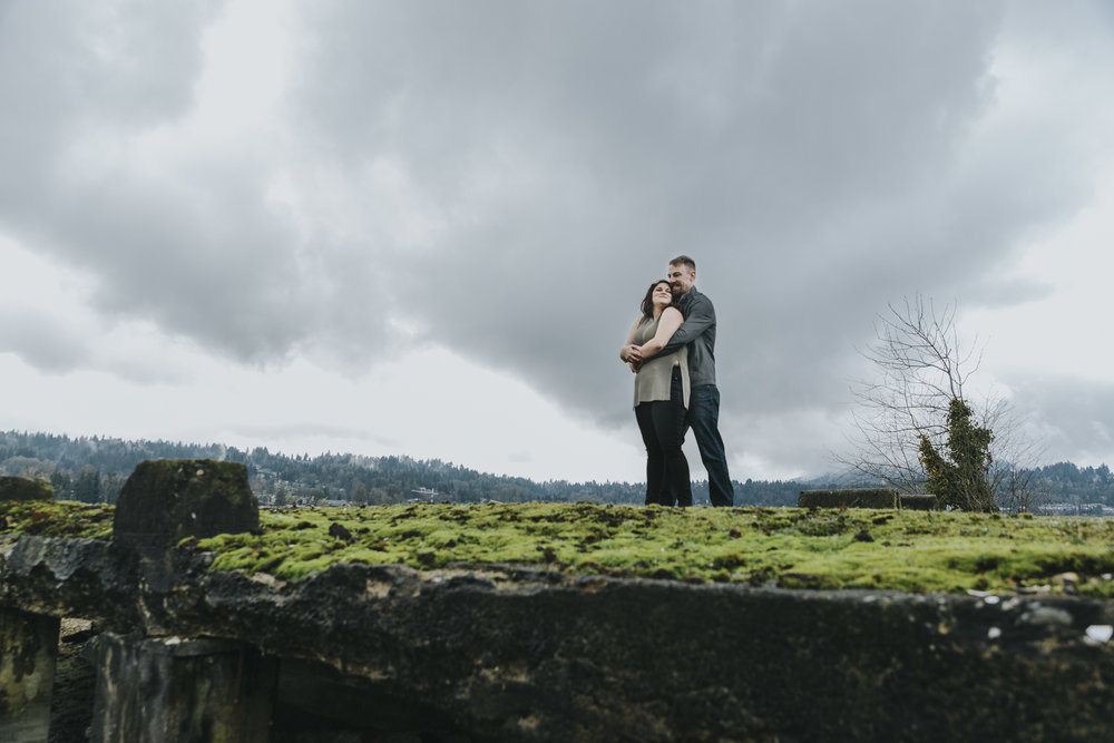 Engagement photography taken at old ruins on ocean inlet. Cloudy skies, romantic poses and muddy shoes.  Photography by Christina Voorhorst of Mimsical Photography  #engagement #ring #cloudyskies #adventure #mountainengagement #river #ocean #water #ruins #abandoned #photography #westcoast #westcoastphotography  #romantic #realemotion #realcouple #genuine #authentic