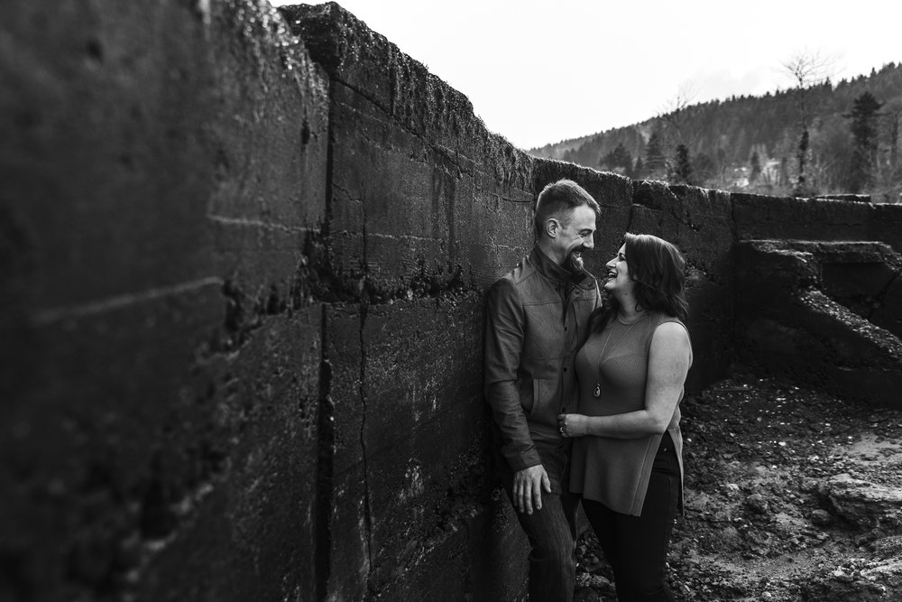 Engagement photography taken at old ruins on ocean inlet. Cloudy skies, romantic poses and muddy shoes. Couple facing each other smiling  Photography by Christina Voorhorst of Mimsical Photography  #engagement #ring #cloudyskies #adventure #mountainengagement #river #ocean #water #ruins #abandoned #photography #westcoast #westcoastphotography  #romantic #realemotion #realcouple #genuine #authentic