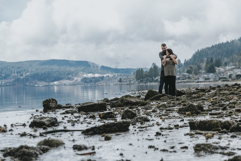 Engagement photography taken at old ruins on ocean inlet. Cloudy skies, romantic poses and muddy shoes. Couple standing on rocks, arms wrapped around each other  Photography by Christina Voorhorst of Mimsical Photography  #engagement #ring #cloudyskies #adventure #mountainengagement #river #ocean #water #ruins #abandoned #photography #westcoast #westcoastphotography  #romantic #realemotion #realcouple #genuine #authentic