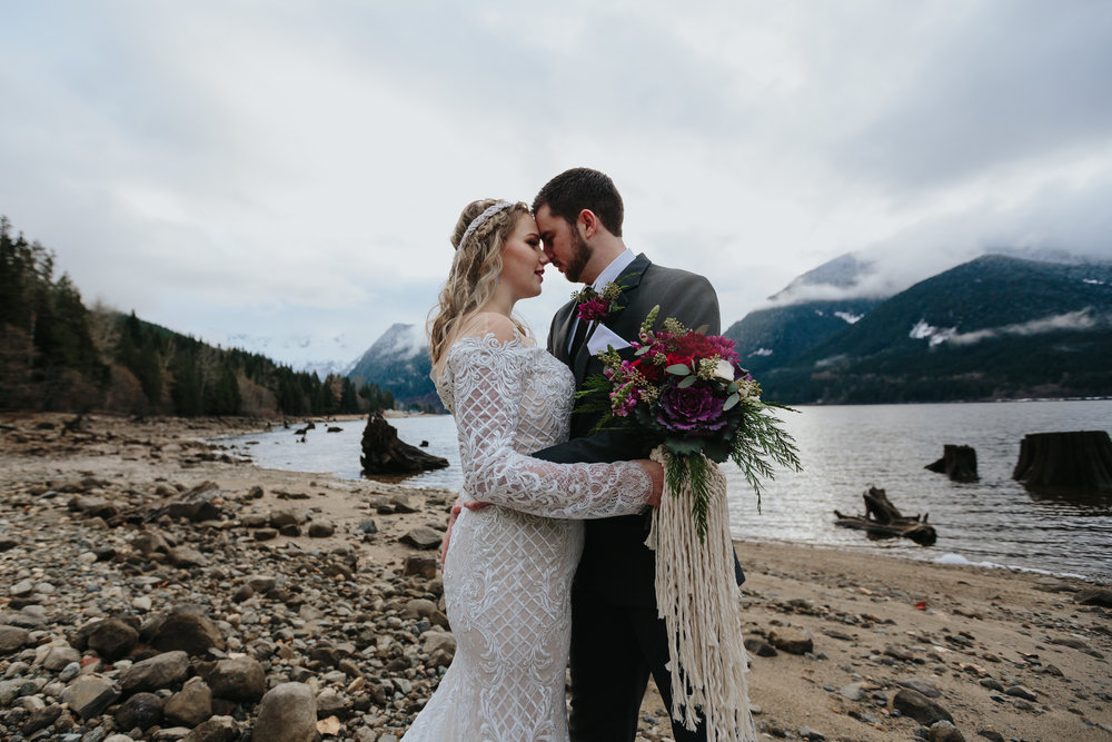 Mountain Lake, Jones Lake Chilliwack British Columbia, Lace Wedding Dress, Grey Suit, Purple Red Rich Flowers, Romantic, Intimate, Adventure session. Lower Mainland, snow  Photography: Mimsical Photography by Christina Voorhorst  Dress: Everything But the Groom Suit: Cardero Clothing Florals: The Lasting Bloom Headpiece: Little Fern Woven Art Makeup: Artistry by Angela Hair: Jill Keech Hair Jewellry: Lost Arrow Designs