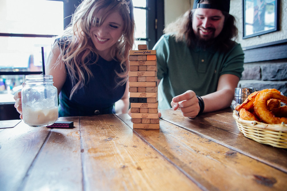Couple playing Jenga in tavern, butterbeer drink.  Genuine Smiles  Storm Crow Tavern Documentary Engagement Photography, Nerd Bar, Board Games by Mimsical Photography. Real stories about Real Couples that are just as unique as they are. #unique #vibrant #personality #nerd #princess #ecclectic #gamer #couple #tavern #vancouver #candid #storytelling