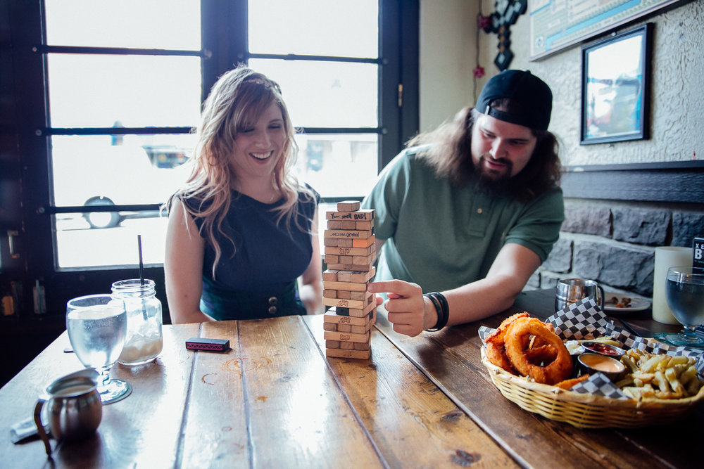 Storm Crow Tavern Jenga game with couple.   Storm Crow Tavern Documentary Engagement Photography, Nerd Bar, Board Games by Mimsical Photography. Real stories about Real Couples that are just as unique as they are. #unique #vibrant #personality #nerd #princess #ecclectic #gamer #couple #tavern #vancouver #candid #storytelling