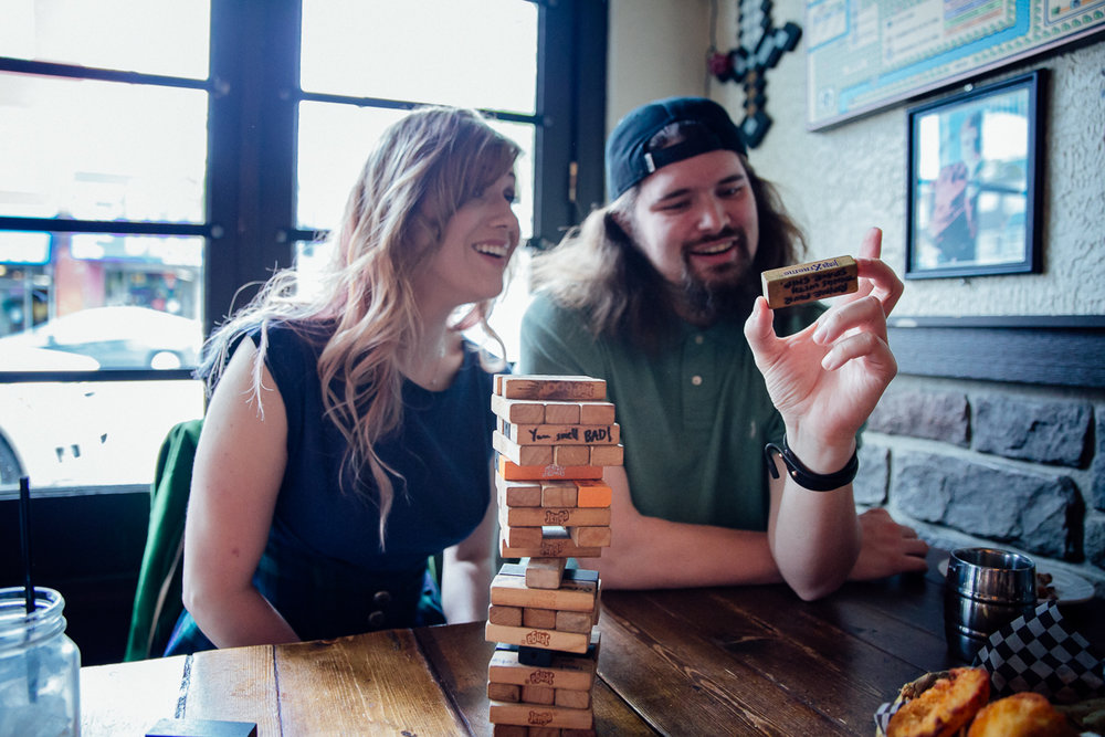 Alternate Jenga - write challenges or dares on the blocks and break the ice with friends.  Storm Crow Tavern Documentary Engagement Photography, Nerd Bar, Board Games by Mimsical Photography. Real stories about Real Couples that are just as unique as they are. #unique #vibrant #personality #nerd #princess #ecclectic #gamer #couple #tavern #vancouver #candid #storytelling
