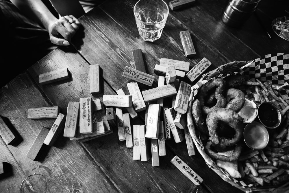 Black and White aftermath of Jenga tower falling over   Storm Crow Tavern Documentary Engagement Photography, Nerd Bar, Board Games by Mimsical Photography. Real stories about Real Couples that are just as unique as they are. #unique #vibrant #personality #nerd #princess #ecclectic #gamer #couple #tavern #vancouver #candid #storytelling