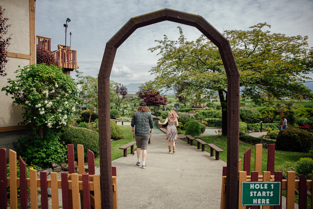 Hole one at Castle Fun park, skipping    Castle Fun Park Documentary Engagement Photography, minigolf date by Mimsical Photography. Real stories about Real Couples that are just as unique as they are. #unique #vibrant #personality #nerd #princess #ecclectic #gamer #couple #minigolf #vancouver #candid #storytelling #connect #datesforcouples #arcade #arcadedate