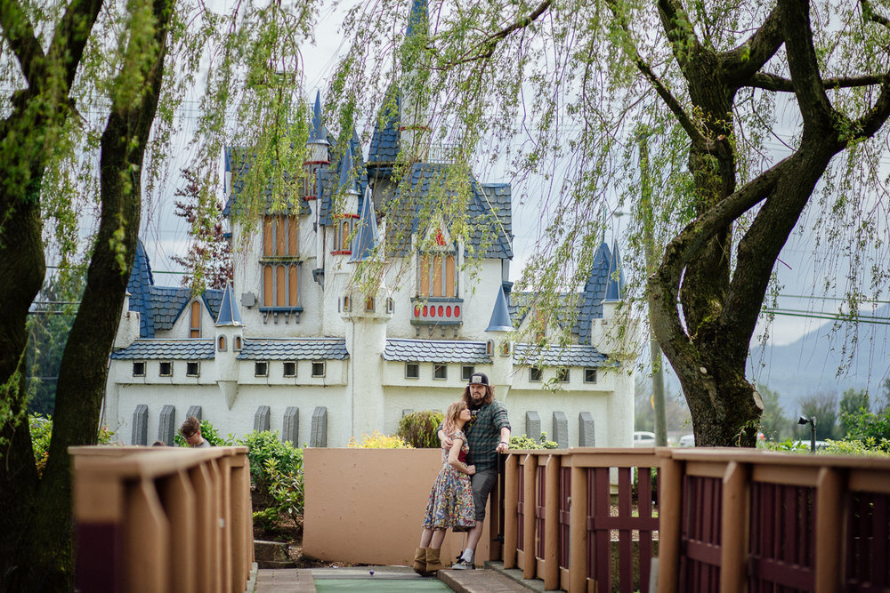 Standing by the Iconic Castle from Castle Fun Park  Castle Fun Park Documentary Engagement Photography, minigolf date by Mimsical Photography. Real stories about Real Couples that are just as unique as they are. #unique #vibrant #personality #nerd #princess #ecclectic #gamer #couple #minigolf #vancouver #candid #storytelling #connect #datesforcouples #arcade #arcadedate