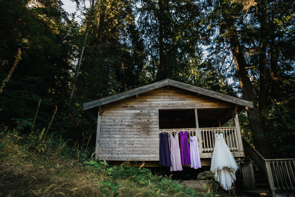 Wedding dress and purple shade bridesmaid dress hanging from rustic cabin    Mimsical Photography Documentary Wedding Photography, Camp Howdy, Belcarra Provincial Park, North Vancouver. Purple and Grey Wedding Colours, Natural Greenery, Rustic Details, Summer, Lace and chiffon, big wedding, greek, lower mainland, british columbia, real, genuine, candid