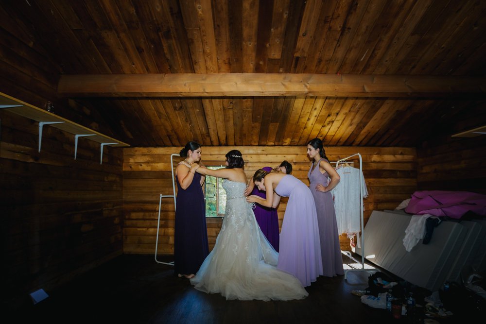 bridesmaids helping bride get dressed   Mimsical Photography Documentary Wedding Photography, Camp Howdy, Belcarra Provincial Park, North Vancouver. Purple and Grey Wedding Colours, Natural Greenery, Rustic Details, Summer, Lace and chiffon, big wedding, greek, lower mainland, british columbia, real, genuine, candid