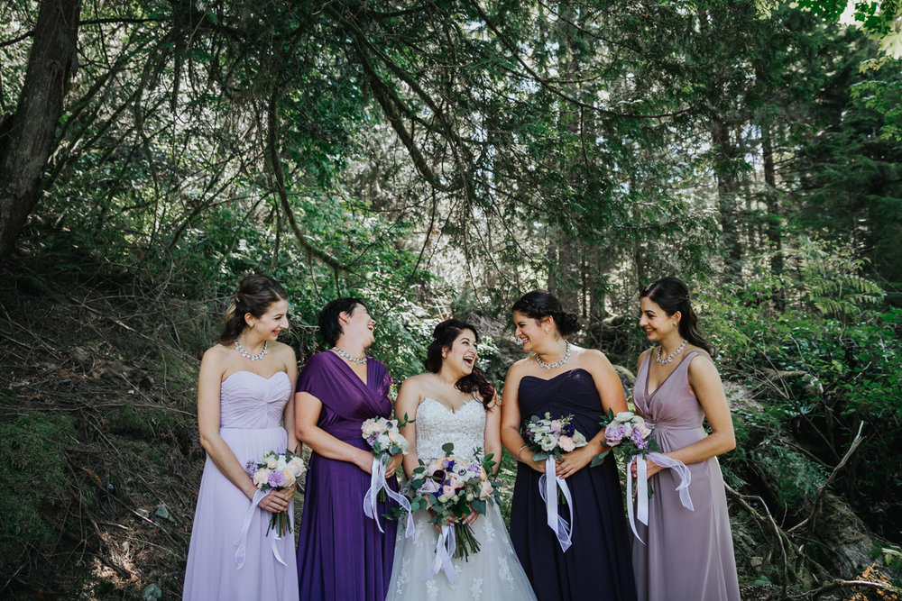 bridesmaid laughing with bride wearing different shades of purple gowns   Mimsical Photography Documentary Wedding Photography, Camp Howdy, Belcarra Provincial Park, North Vancouver. Purple and Grey Wedding Colours, Natural Greenery, Rustic Details, Summer, Lace and chiffon, big wedding, greek, lower mainland, british columbia, real, genuine, candid