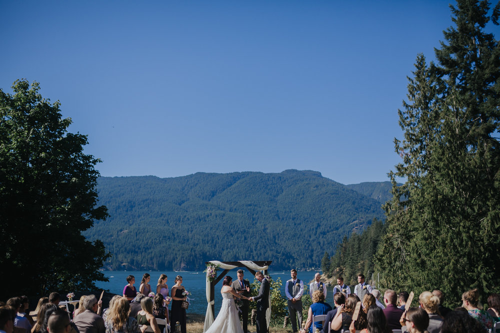 Wedding ceremony at Camp Howdy overlooking inlet  Mimsical Photography Documentary Wedding Photography, Camp Howdy, Belcarra Provincial Park, North Vancouver. Purple and Grey Wedding Colours, Natural Greenery, Rustic Details, Summer, Lace and chiffon, big wedding, greek, lower mainland, british columbia, real, genuine, candid