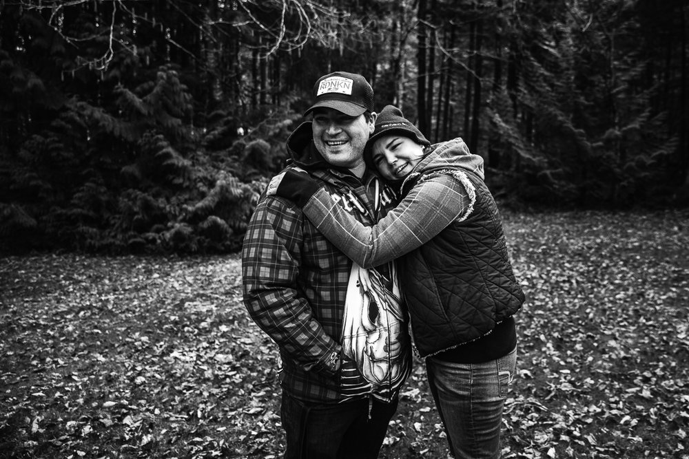 Man wearing plaid and black baseball hat being hugged by a woman wearing paid sweater and black jacket in black and white in the forest. Sasquatch Park Hicks Lake Camping Engagement Session Plaid Fishing Child Forest Fun Candid Documentary-42.JPG