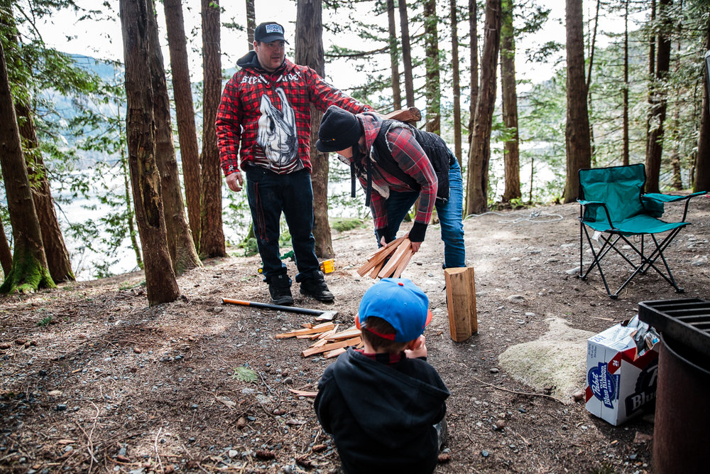 Father balancing piece of wood on mother's back while chopping firewood while little boy watches at Sasquatch Park Hicks Lake Camping Engagement Session Plaid Fishing Child Forest Fun Candid Documentary-90.JPG