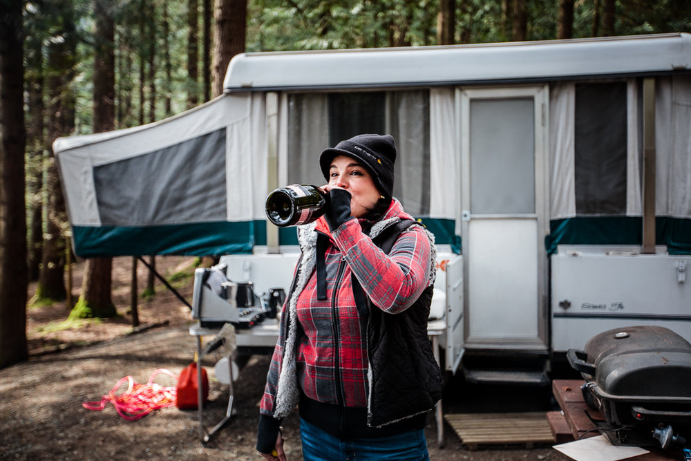 Woman wearing red plaid and black vest drinking straight from a champagne bottle standing in front of an old tent trailer Sasquatch Park Hicks Lake Camping Engagement Session Plaid Fishing Child Forest Fun Candid Documentary-116.JPG