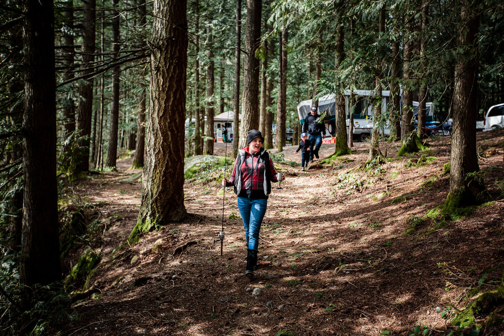 Woman walking down forest trail with fishing rod and metal wine glass .Sasquatch Park Hicks Lake Camping Engagement Session Plaid Fishing Child Forest Fun Candid Documentary-118.JPG