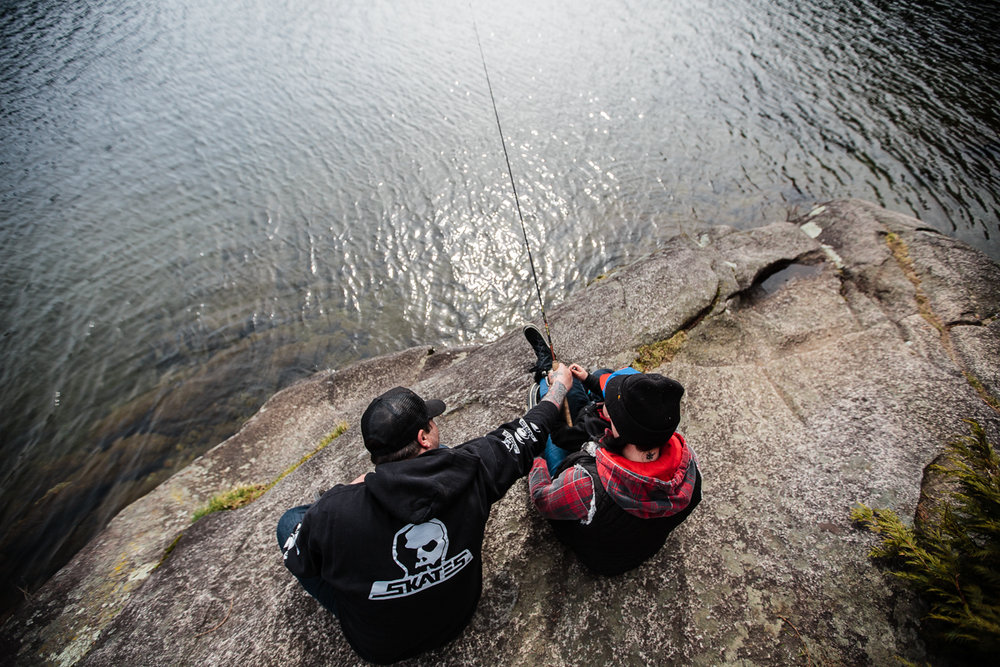 Man in black hoodie and Woman in red plaid and black hat sitting on rock outcropping fishing into mountain lake at Sasquatch Park Hicks Lake Camping Engagement Session Plaid Fishing Child Forest Fun Candid Documentary-124.JPG
