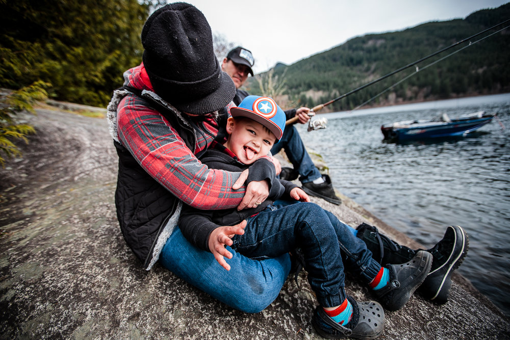 Mom in red plaid sweater and black toque hugging little boy sitting in her lap while sitting on a rock by a lack at Sasquatch Park Hicks Lake Camping Engagement Session Plaid Fishing Child Forest Fun Candid Documentary-136.JPG