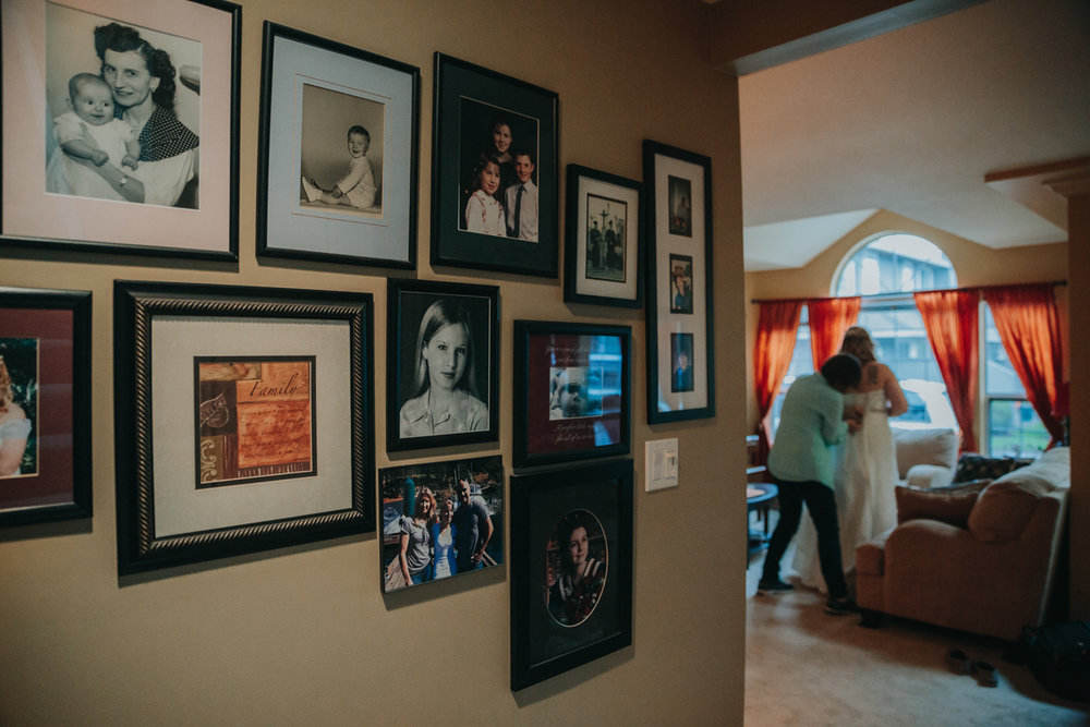 Family wall of photographs in the foreground while bride gets laced into her dress in the background east delta hall wedding by mimsical photography