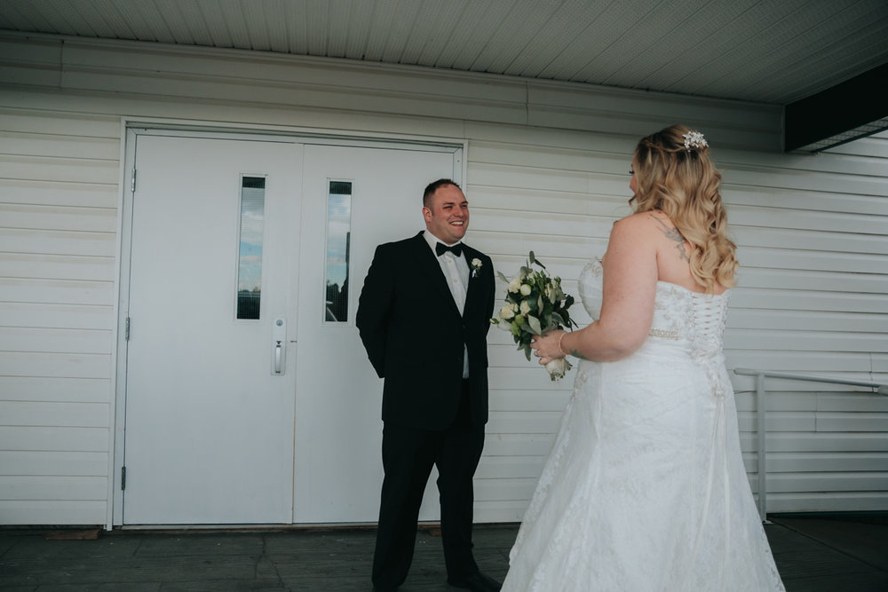 Groom's reaction to seeing bride during first look in front of East Delta Hall, Ladner wedding by mimsical photography