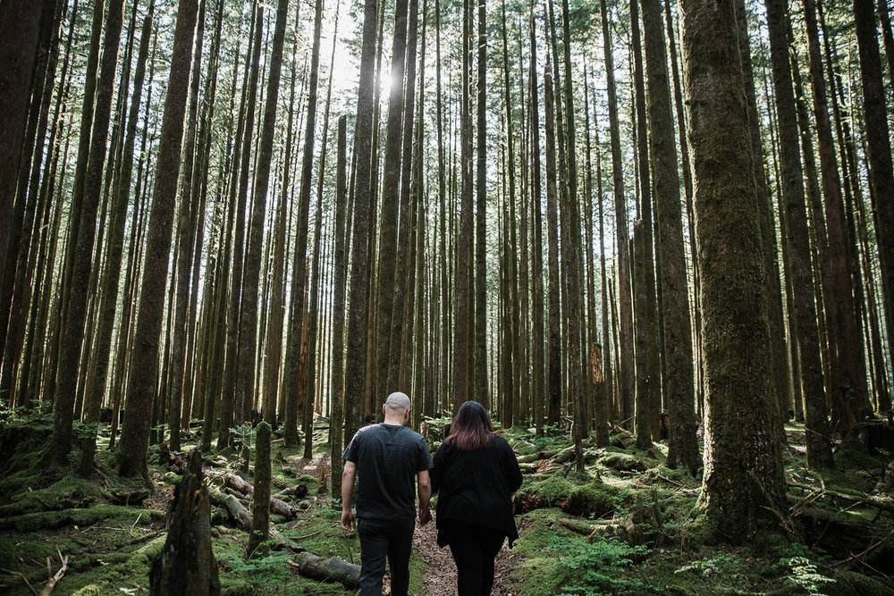 Couple holding hands walking through tall trees with moss covered ground during spring engagement photography at  Spirea Nature Trail in Golden Ears Provincial Park in British Columbia by Mimsical Photography  #PNW #Engaged #couple #plussize #ring