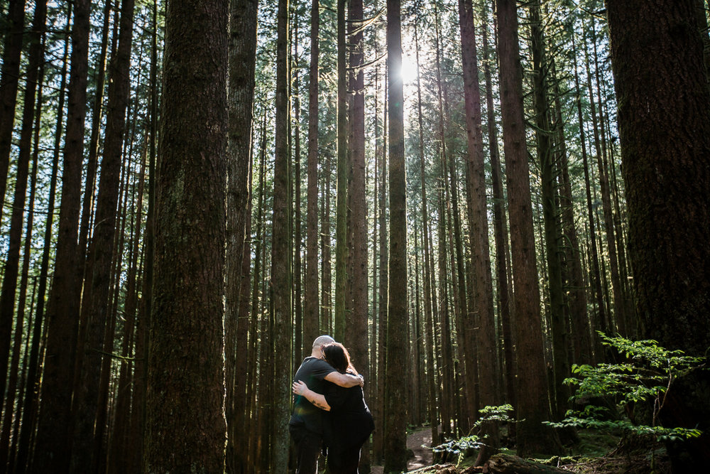 Couple hugging as sun filters down through forest in a romantic pose during spring engagement photography at  Spirea Nature Trail in Golden Ears Provincial Park in British Columbia by Mimsical Photography