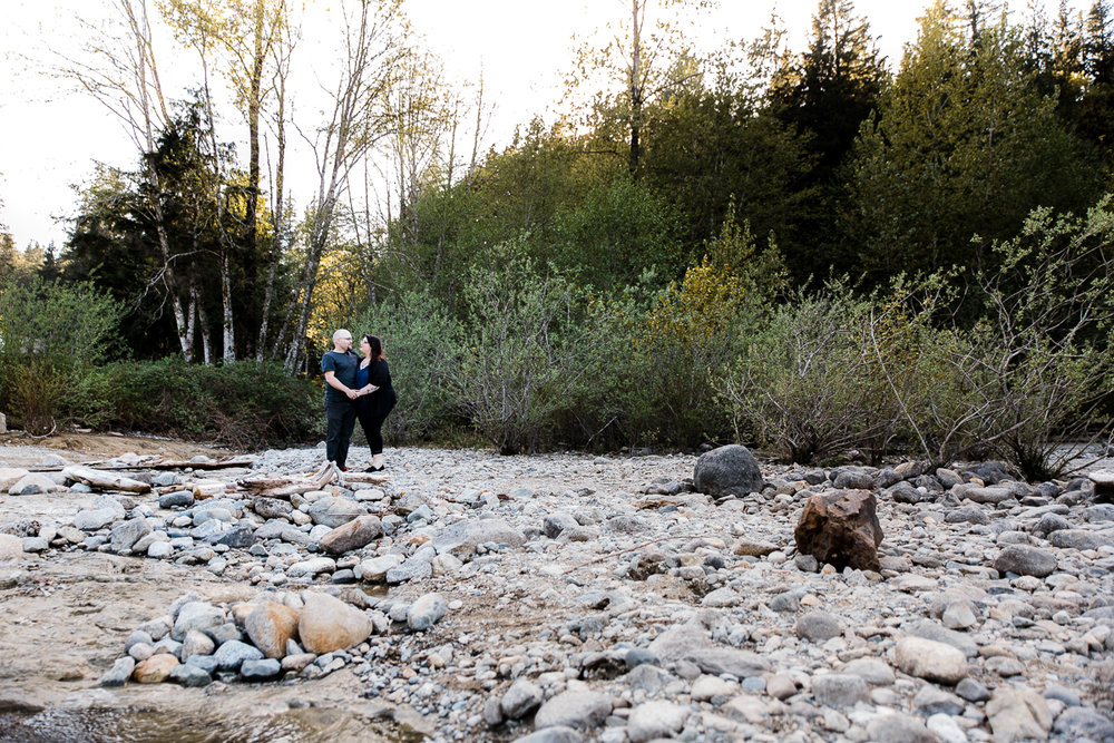 couple holding hands beside beach rocky stream with forest behind during spring engagement photography at  Alouette Lake in  Golden Ears Provincial Park in British Columbia by Mimsical Photography