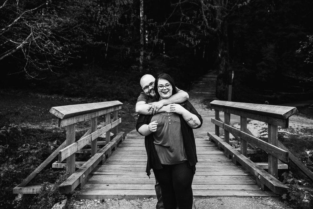 Fun couple pose black and white man standing behind girl hugging and smiling with laughter standing by an old bridge during spring engagement photography at  Alouette Lake in  Golden Ears Provincial Park in British Columbia by Mimsical Photography