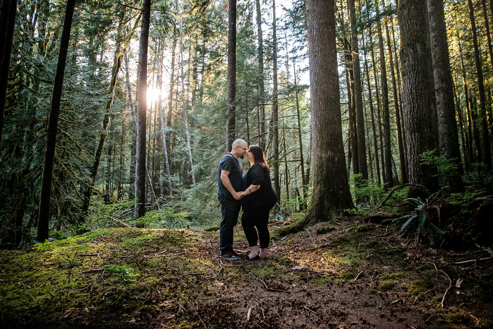 Couple holding hands nose to nose romantic couple pose plus size standing in lush forest during spring engagement photography at  Alouette Lake in  Golden Ears Provincial Park in British Columbia by Mimsical Photography
