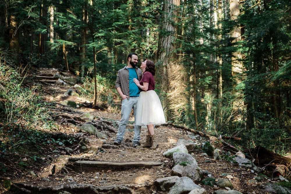 Girl wearing hiking boots, white tulle skirt and maroon red top laughing while looking at a bearded man with plaid shirt while standing on a rustic stairs in the forest during their engagement photography session with Mimsical Photography in their backyard forest on the side of north vancouver mountain on a sunny day.