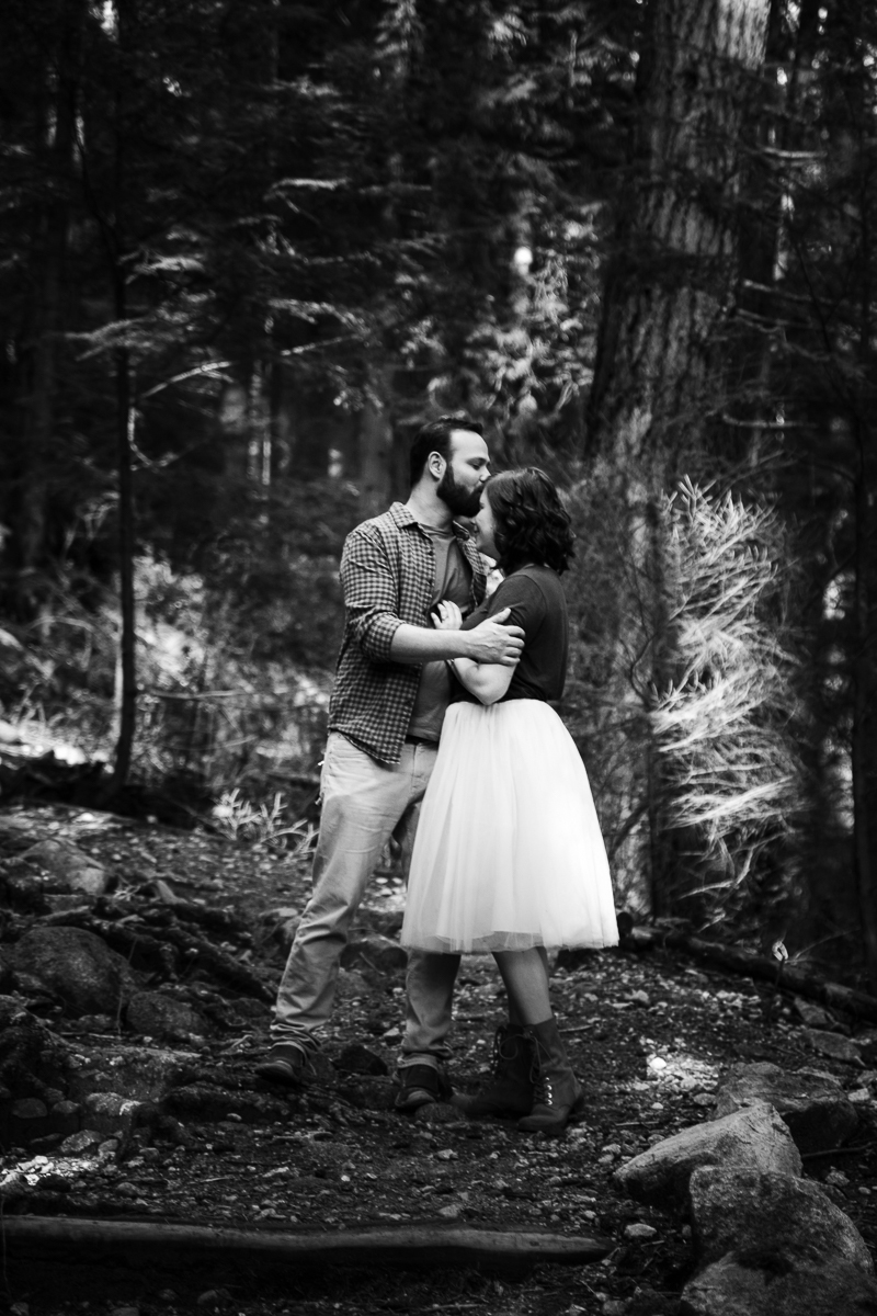 Black and white romantic image of man kissing woman on the top of her forehead during their engagement photography session with Mimsical Photography in their backyard forest on the side of north vancouver mountain on a sunny day.