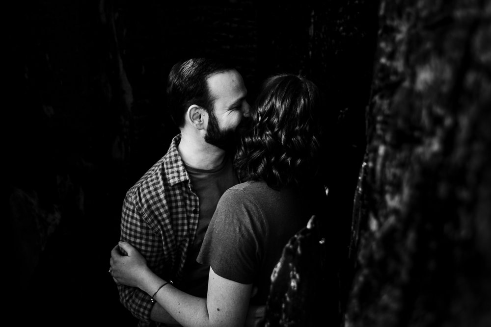 Up close image of man kissing the side of his fiance's temple black and white while laughing in a romantic pose during their engagement photography session with Mimsical Photography in their backyard forest on the side of north vancouver mountain on a sunny day.