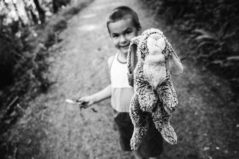 Black and white photo of boy holding up stuffed bunny rabbit during a Family Photography session at Aldergrove Bowl Provincial park in Abbotsford, British Columbia on a spring day  #vancouverfamilyphotographer #metrovancouver #candidfamilyphotos #lifestylefamily by mimsical photography christina voorhorst