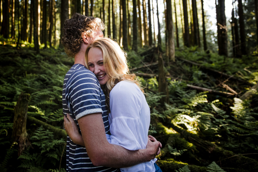 Young romantic couple standing in woods between mossy trees and ferns hugging each other face to face and laughing wearing white shirt and blue jeans during an adventure engagement photography at bridal veil falls lookout in chilliwack agassiz british columbia  Top BC Wedding Photographers in Vancouver Wedding Photographer Chilliwack Wedding Photographer Candid Shots unique engagement photos #pnw #couple #engaged #fraservalley #pnw #romantic