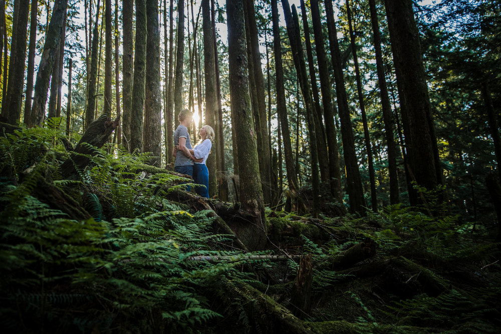 Young romantic couple standing in woods between mossy trees and ferns hugging each other wearing white shirt and blue jeans during an adventure engagement photography at bridal veil falls lookout in chilliwack agassiz british columbia  Top BC Wedding Photographers in Vancouver Wedding Photographer Chilliwack Wedding Photographer Candid Shots unique engagement photos #pnw #couple #engaged #fraservalley #pnw #romantic