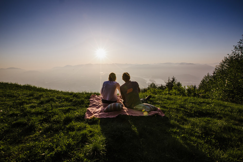 Young romantic couple sitting on picnic blanket watching the sunset wearing white shirt and blue jeans during an adventure engagement photography at bridal veil falls lookout in chilliwack agassiz british columbia  Top BC Wedding Photographers in Vancouver Wedding Photographer Chilliwack Wedding Photographer Candid Shots unique engagement photos #pnw #couple #engaged #fraservalley #pnw #romantic