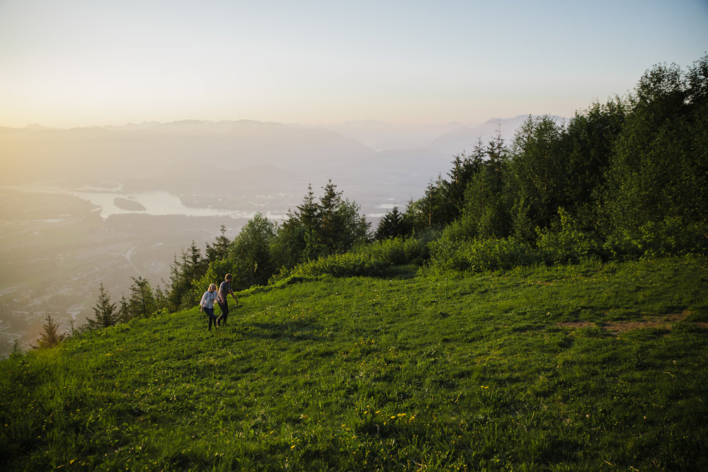 Young romantic couple walking up grassy mountain field holding hands wearing white shirt and blue jeans during an adventure engagement photography at bridal veil falls lookout in chilliwack agassiz british columbia sunset  Top BC Wedding Photographers in Vancouver Wedding Photographer Chilliwack Wedding Photographer Candid Shots unique engagement photos #pnw #couple #engaged #fraservalley #pnw #romantic