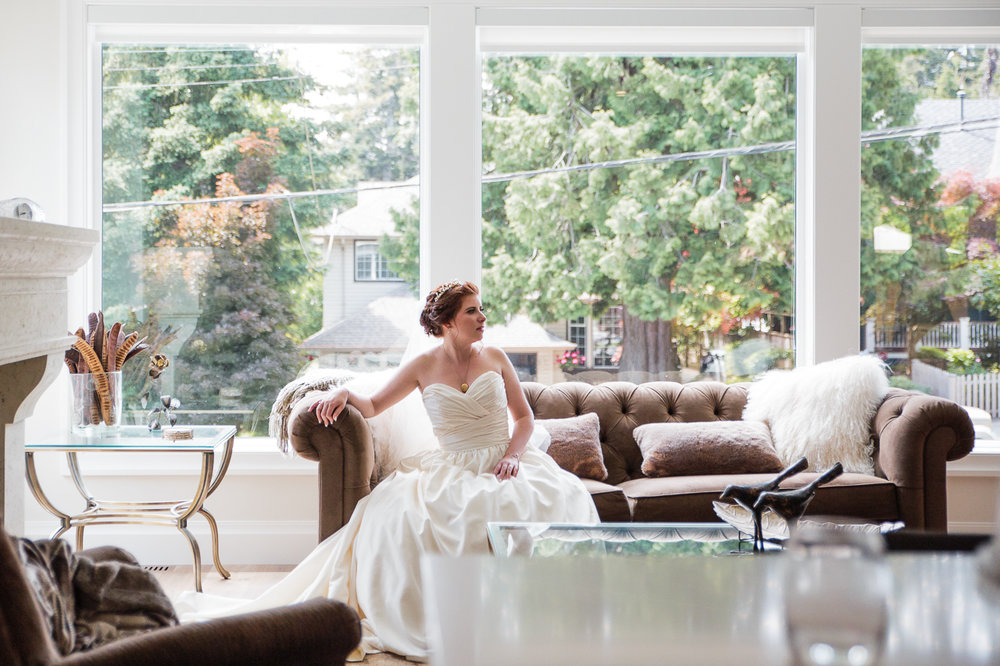bride waiting in luxury home on leather couch by the windows before outdoor summer wedding at Kwomais Point Park in Ocean Park Surrey British Columbia by Mimsical Photography who is a wedding photographer from Langley, BC that has a candid and documentary fun style.