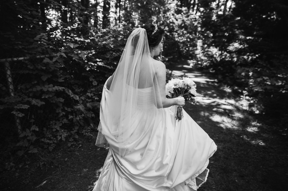 bride carrying dress through forest before outdoor summer wedding at Kwomais Point Park in Ocean Park Surrey British Columbia by Mimsical Photography who is a wedding photographer from Langley, BC that has a candid and documentary fun style.