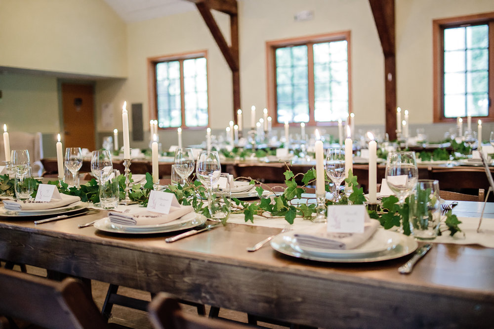 long table place settings wooden table rustic decor green decor and real candles before wedding reception at Kwomais Hall by Kwomais Point Park in Ocean Park Surrey by best wedding photographer from Langley Mimsical Photography Christina Voorhorst style is documentary candid and fun photos