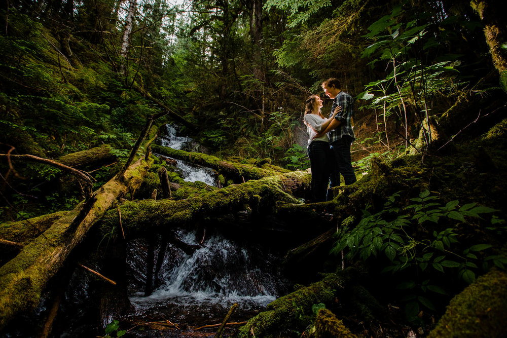 couple standing by small creek in the middle of lush BC forest with moss covered logs and ferns around them light by off camera flash  by   Folley Creek  near Folley Lake along Folley Service Road in Chilliwack British Columbia during outdoor engagement photography session in the mountains with Mimsical Photography.    Outdoor adventure photographer based in Langley, British Columbia. Real fun engagement photos for outdoor enthusiasts in the lower mainland. romantic pictures of couple