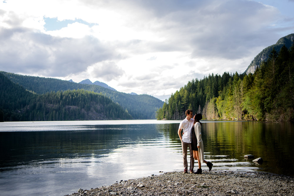 couple kissing Buntzen Lake Landscape behind them evening still water wearing white button down shirt and black dress with hat during fun and romantic engagement photo shoot at Buntzen Lake, Port Moody, Anmore British Columbia by best couples photographer Mimsical Photography