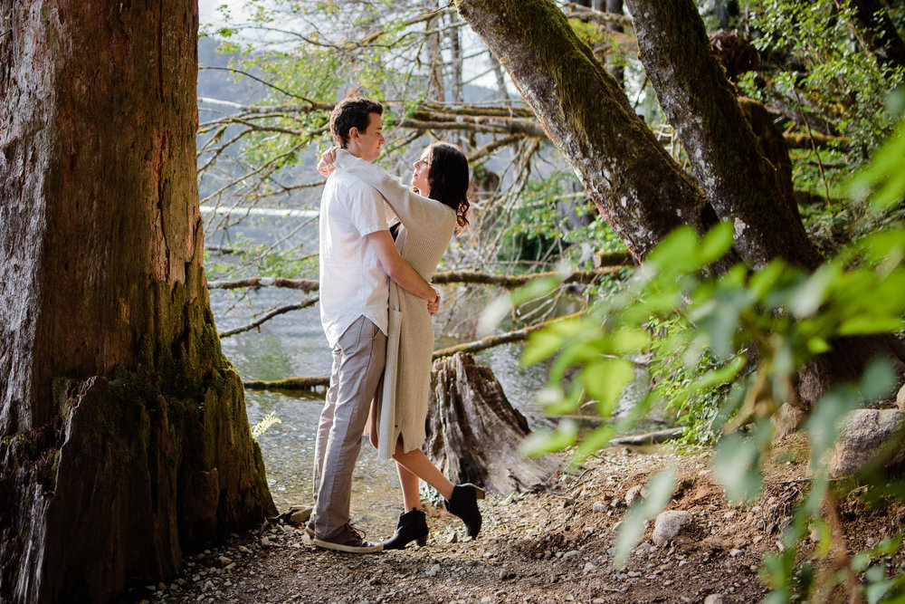 Couple pose facing each other arms around neck edge of water by Buntzen Lake during evening the still water wearing white button down shirt and black dress with hat during fun and romantic engagement photo shoot at Buntzen Lake, Port Moody, Anmore British Columbia by best couples photographer Mimsical Photography